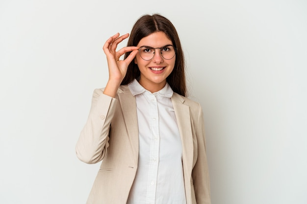 Young business caucasian woman isolated on white background excited keeping ok gesture on eye.