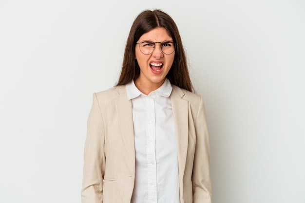 Young business caucasian woman isolated on white background screaming very angry and aggressive.