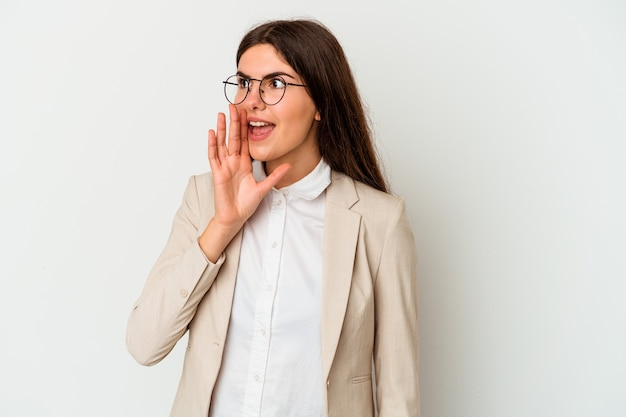 Young business caucasian woman isolated on white background shouting and holding palm near opened mouth.