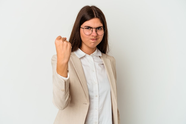 Young business caucasian woman isolated on white background showing fist to camera, aggressive facial expression.