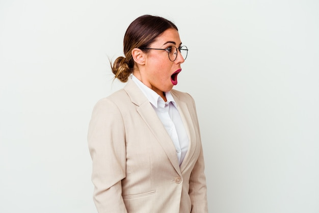 Young business caucasian woman isolated on white being shocked because of something she has seen.