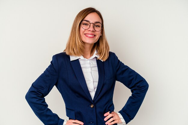Young business caucasian woman isolated on white confident keeping hands on hips.