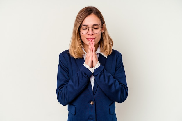 Young business caucasian woman isolated on white holding hands in pray near mouth, feels confident.