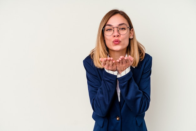 Young business caucasian woman isolated on white wall folding lips and holding palms to send air kiss.