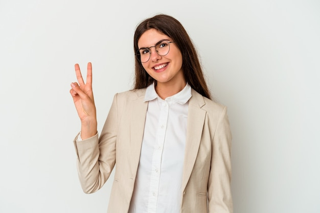 Young business caucasian woman isolated on white wall joyful and carefree showing a peace symbol with fingers