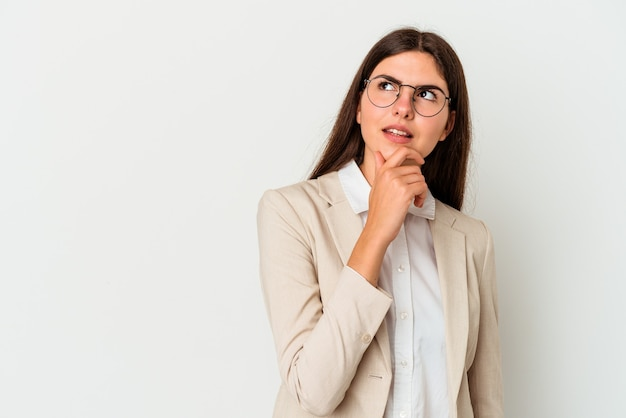Young business caucasian woman isolated on white wall looking sideways with doubtful and skeptical expression