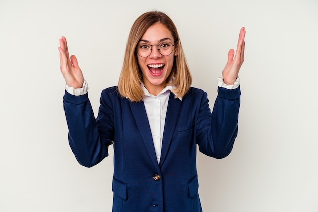 Young business caucasian woman isolated on white wall receiving a pleasant surprise, excited and raising hands