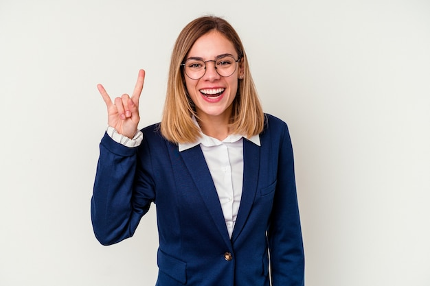 Young business caucasian woman isolated on white wall showing a horns gesture