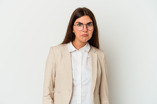 Young business caucasian woman isolated on white wall shrugs shoulders and open eyes confused