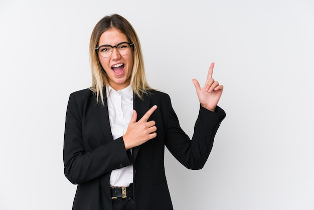興奮と欲望を表現し、コピースペースに人差し指で指している若いビジネス白人女性。