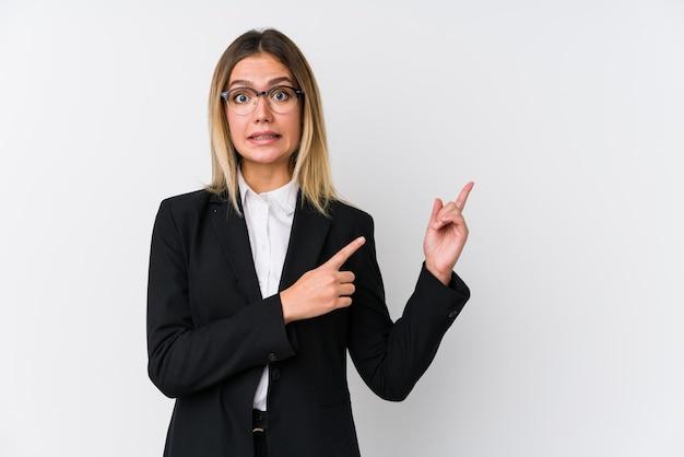 若いビジネス白人女性は、人差し指でコピースペースを指差してショックを受けました。