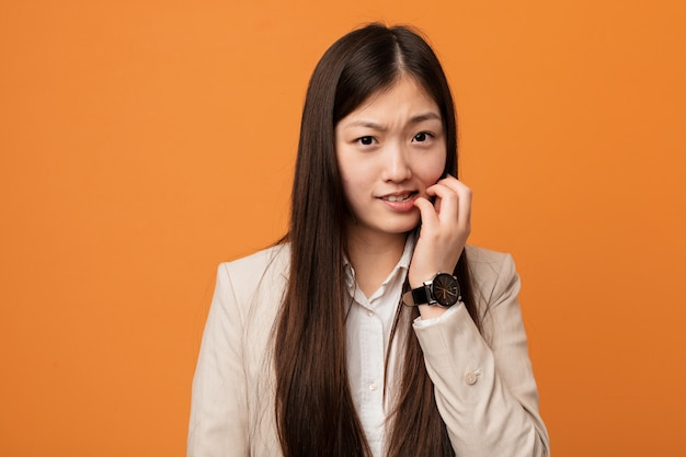 Young business chinese woman biting fingernails, nervous and very anxious.
