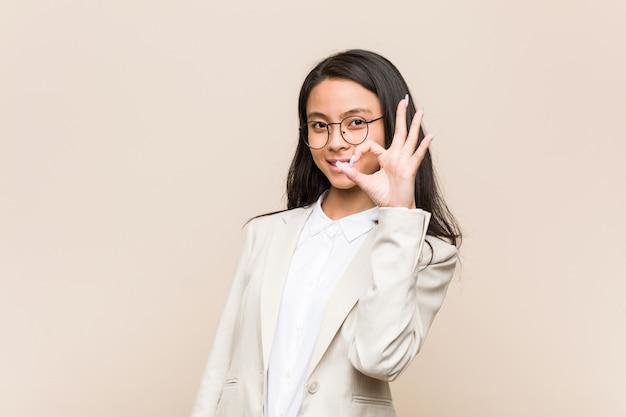 Женщина молодого дела китайская жизнерадостная и уверенно показывая о кеы жест.