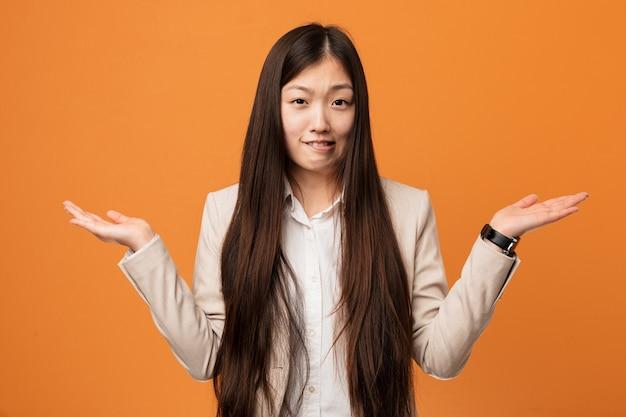 젊은 비즈니스 중국 여자 혼란과 의심 그에게 복사 공간을 잡고 손을 제기.
