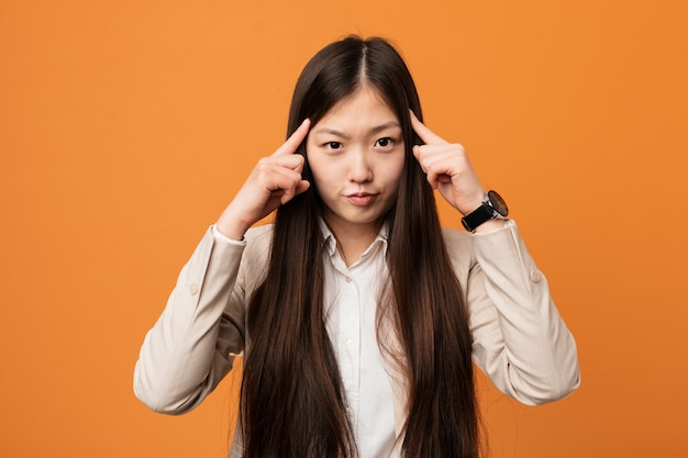 Young business chinese woman focused on a task, keeping him forefingers pointing head.