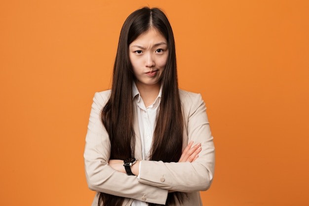 Young business chinese woman frowning face in displeasure, keeps arms folded.