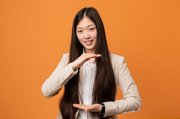 Young business chinese woman holding something with both hands, product presentation