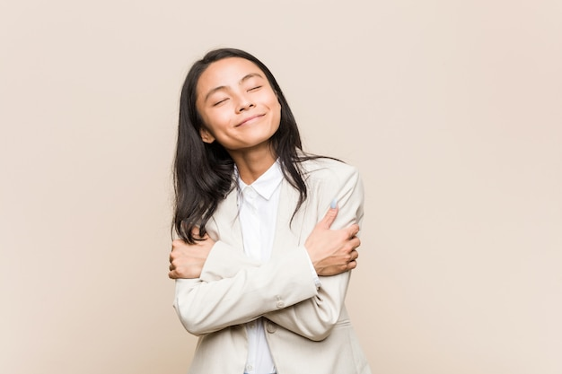 Young business chinese woman hugs, smiling carefree and happy.