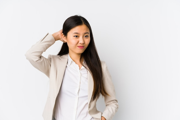 Young business chinese woman isolated touching back of head, thinking and making a choice.