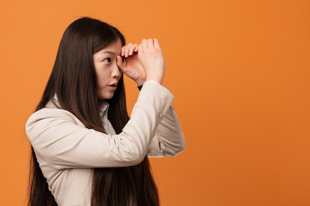 Young business chinese woman looking far away keeping him hand on forehead.
