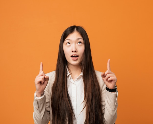 Young business chinese woman pointing upside with opened mouth.