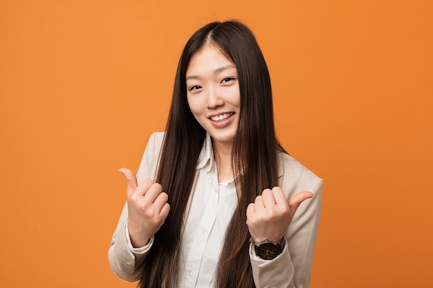 Young business chinese woman raising both thumbs up, smiling and confident.