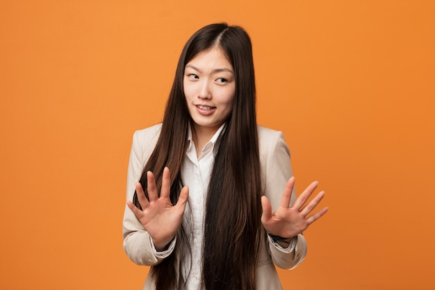 Young business chinese woman rejecting someone showing a gesture of disgust.