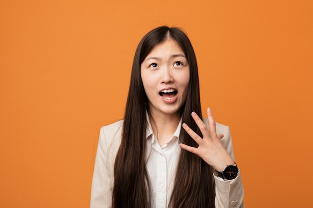 Young business chinese woman screaming with rage.