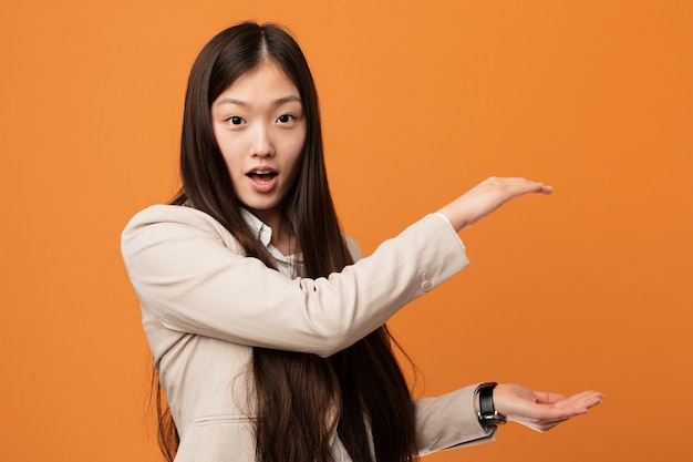 Young business chinese woman shocked and amazed holding a copy space between hands.