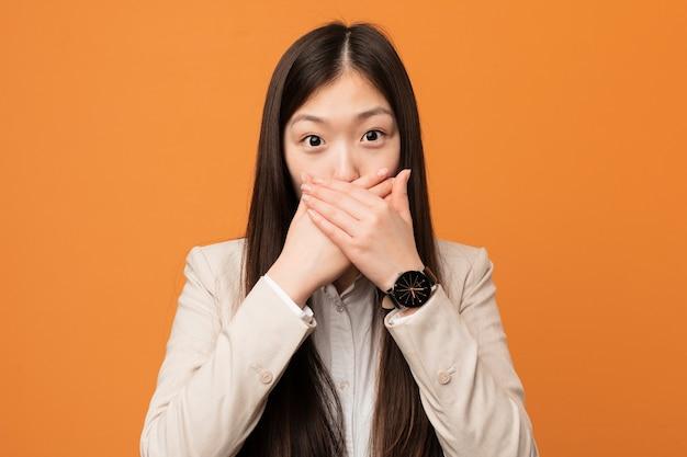 Молодая бизнес-китаянка шокировала рот руками.