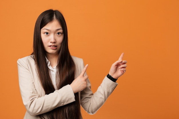Young business chinese woman shocked pointing with index fingers to a copy space.