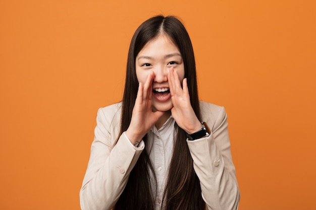 Young business chinese woman shouting excited to front.