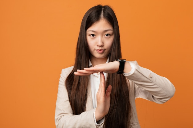Young business chinese woman showing a timeout gesture.