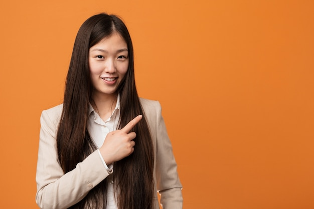Young business chinese woman smiling and pointing aside
