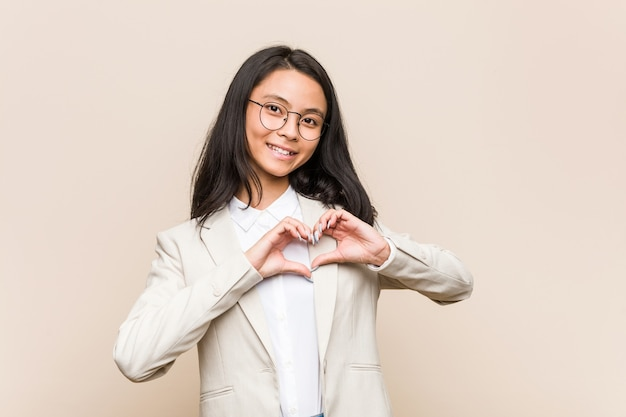 Young business chinese woman smiling and showing a heart shape with hands.