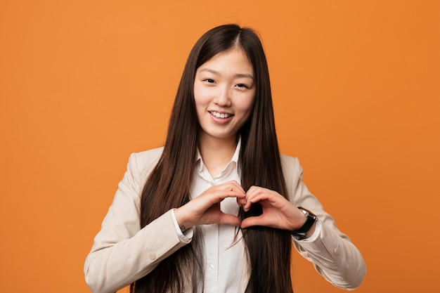 Young business chinese woman smiling and showing a heart shape with him hands.