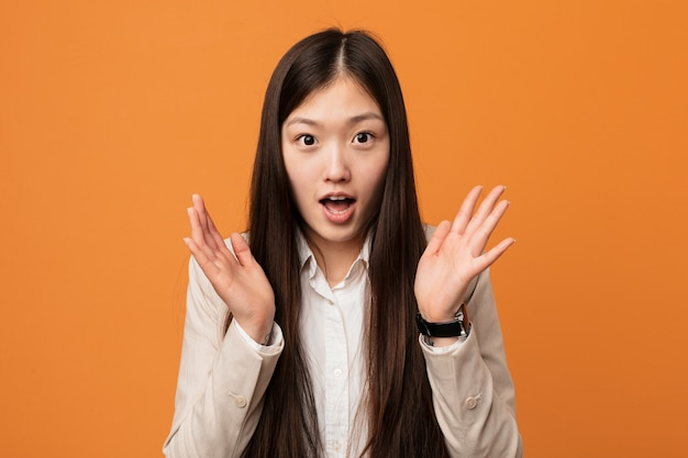 Young business chinese woman surprised and shocked.