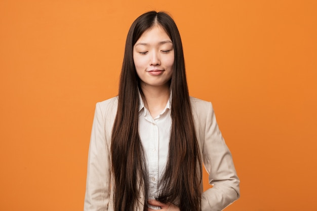 Young business chinese woman touches tummy, smiles gently, eating and satisfaction concept.