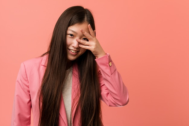 Young business chinese woman wearing pink suit blink at the camera through fingers, embarrassed covering face.