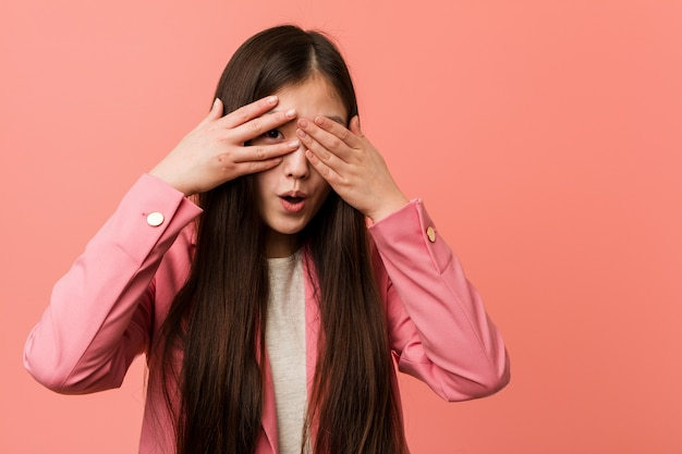 Young business chinese woman wearing pink suit blink through fingers frightened and nervous.