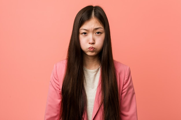 Young business chinese woman wearing pink suit blows cheeks, has tired expression.