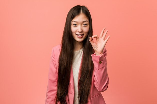 Young business chinese woman wearing pink suit cheerful and confident showing ok gesture.