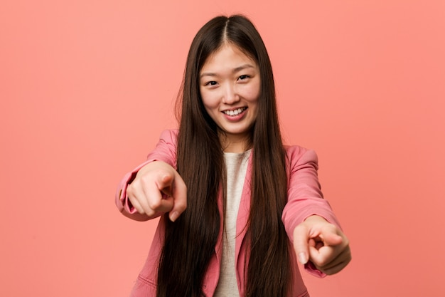 Young business chinese woman wearing pink suit cheerful smiles pointing to front.