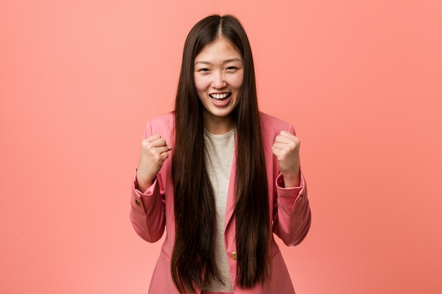 Young business chinese woman wearing pink suit cheering carefree and excited.