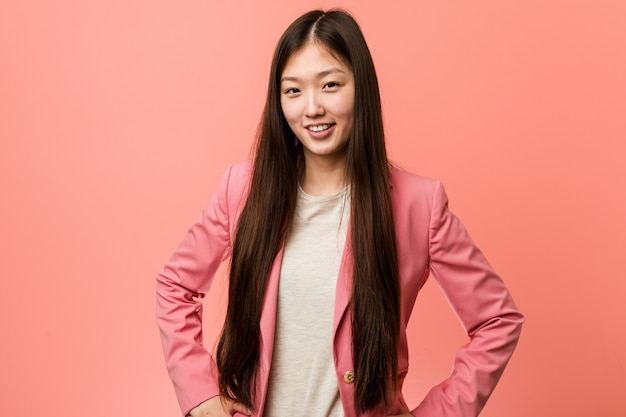 Young business chinese woman wearing pink suit confident keeping hands on him hips.