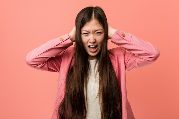 Young business chinese woman wearing pink suit covering ears with hands trying not to hear too loud sound.