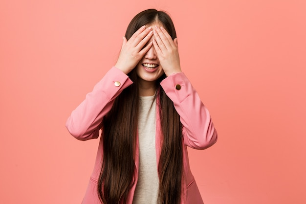 Young business chinese woman wearing pink suit covers eyes with hands, smiles broadly waiting for a surprise.