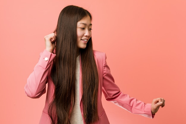 Young business chinese woman wearing pink suit dancing and having fun.