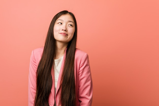 Young business chinese woman wearing pink suit dreaming of achieving goals and purposes