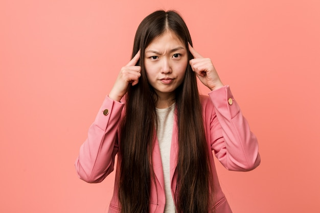 Young business chinese woman wearing pink suit focused on a task, keeping him forefingers pointing head